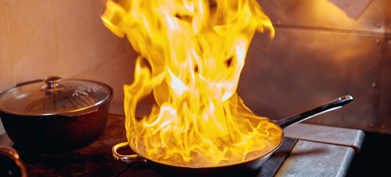 Flambe. Fire in frying pan. Professional chef in a commercial kitchen cooking. Man frying food in flaming pan on hob in outdoor kitchen