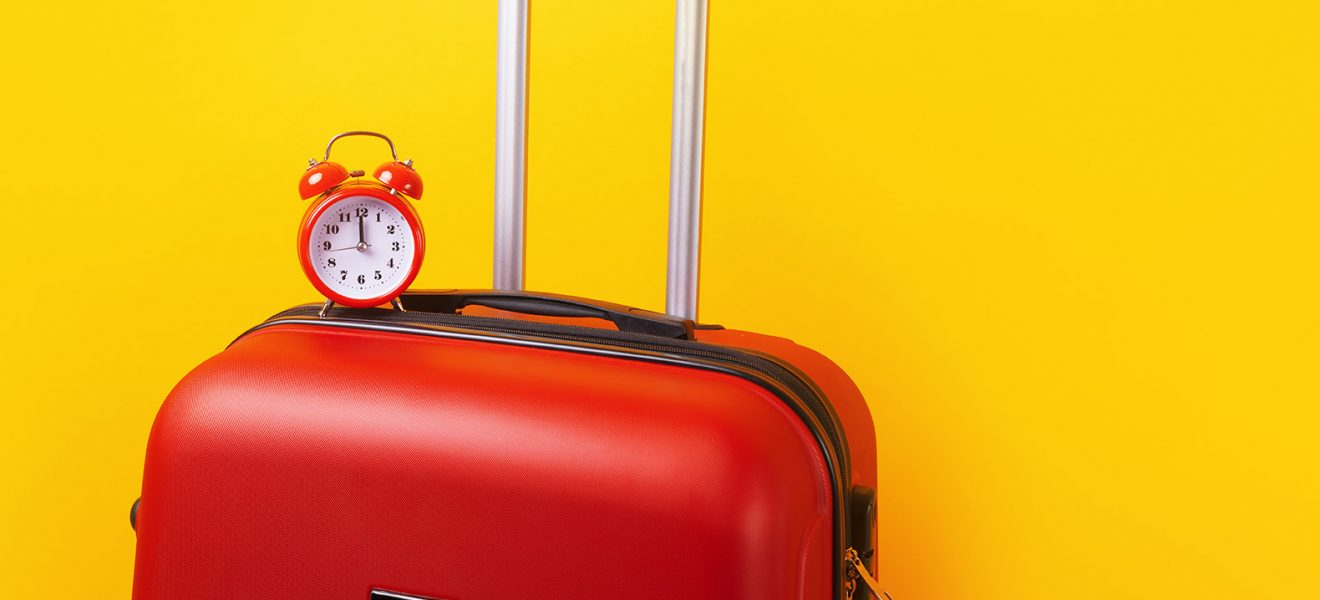 Travel case with alarm clock  over yellow background. Time to voyage. Voyage concept. Retro alarm clock with red suitcase, panoramic mock-up