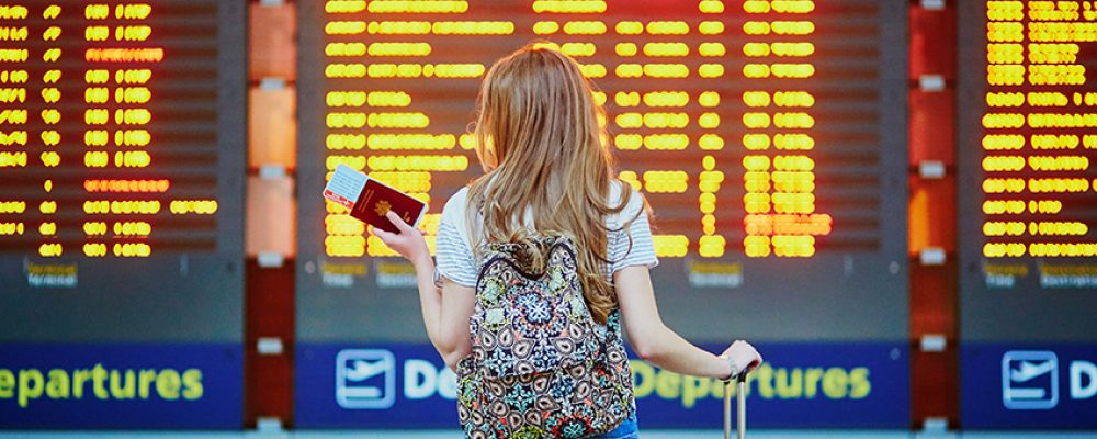 Beautiful young tourist girl with backpack and carry on luggage in international airport near flight information board