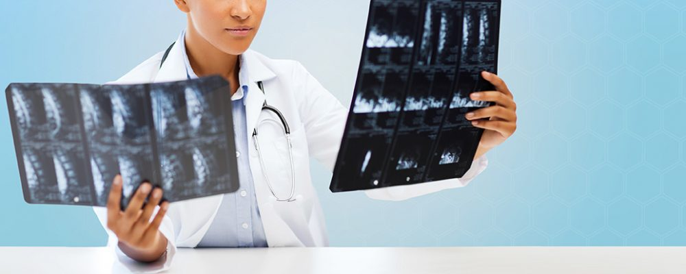 healthcare, medicine, people and radiology concept - african american female doctor looking at x-rays over blue background